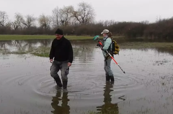Two people walking through flooded field at excavation site